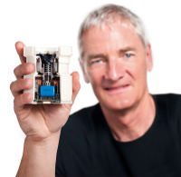 James Dyson holding a digital motor which relies on algorithm controls to measure the speed of impeller rotation and fire digital pulses to magnets which make sure the impeller maintains optimum speed