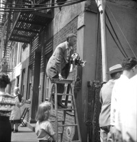 Frame from a contact sheet featuring the photojournalist Weegee seeking a better angle from a stepladder, during the filming of Jules Dassin's film The Naked City, July 1947, New York City. Kubrick would hire Weegee 15 years later as a set photographer fo